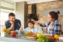 Family at home leaning on table in kitchen together parents looking at son mixing salad smiling proud royalty free stock images