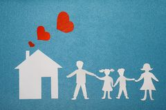 Family and home love concept. Paper house and family on blue textured background. Dad, mom, daughter and son hold hands. Royalty Free Stock Photos