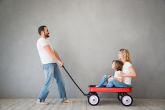 Family Home Moving Day House Concept. Happy family playing into new home. Father, mother and child having fun together. Moving house day and express delivery Stock Photography