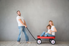 Family Home Moving Day House Concept. Happy family playing into new home. Father, mother and child having fun together. Moving house day and express delivery Royalty Free Stock Image