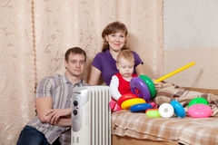 Family   at home near oil heater Stock Photography
