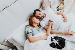 Family couple sleeping in bed together with cat. Family and home pets concept. Top view portrait of men and women sleeping in bed with favorite black and white royalty free stock photo