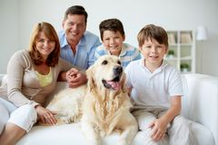 Family at home. Portrait of happy family with their pet having rest at home Royalty Free Stock Photos
