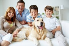 Family at home. Portrait of happy family with their pet having rest at home Royalty Free Stock Photography