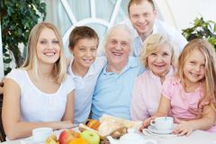 Family at home. Portrait of senior and young couples with their children having dinner at home Royalty Free Stock Image