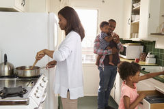 Family At Home Preparing Meal In Kitchen Together Stock Images