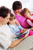 Family at home reading book Royalty Free Stock Photos