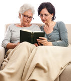 Family at home reading book two women senior adult Royalty Free Stock Photo