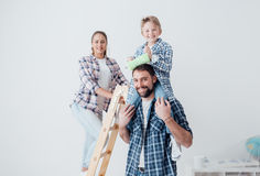 Family home renovation. Happy family renovating their new home, they are posing together with a ladder and a paint roller, the father is piggybacking his son Royalty Free Stock Image