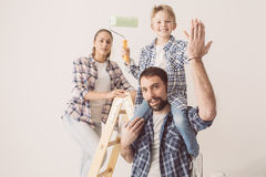 Family home renovation. Happy family renovating their new home, they are posing together with a ladder and a paint roller, the father is piggybacking his son Royalty Free Stock Photos