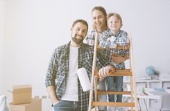 Family and home renovation. Happy young family doing a home makeover, they are posing together, the men is holding a paint roller and the women is holding her stock photo