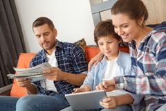 Family at home sitting on sofa in living room together mother and son browsing internet on digital tablet cheerful while stock photography