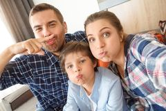 Family at home sitting on sofa in living room together taking selfie photos grimacing joyful close-up royalty free stock images