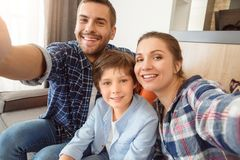 Family at home sitting on sofa in living room together taking selfie photos looking camera happy close-up royalty free stock photos