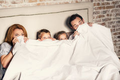 Family at home under coverlet Royalty Free Stock Photo