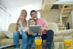 Family at home using tablet computer. Happy young family using tablet computer at modern  home for playing games and education Royalty Free Stock Photography