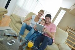 Family at home using tablet computer. Happy young family using tablet computer at modern  home for playing games and education Stock Photography
