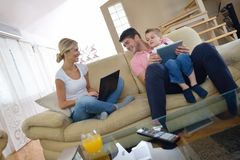Family at home using tablet computer. Happy young family using tablet computer at modern  home for playing games and education Stock Photo