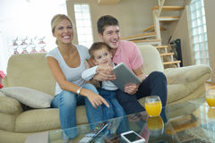 Family at home using tablet computer. Happy young family using tablet computer at modern  home for playing games and education Stock Image