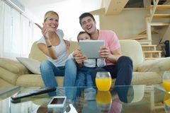 Family at home using tablet computer. Happy young family using tablet computer at modern  home for playing games and education Royalty Free Stock Image