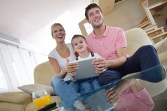 Family at home using tablet computer. Happy young family using tablet computer at modern  home for playing games and education Stock Photos