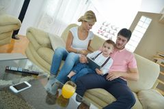 Family at home using tablet computer. Happy young family using tablet computer at modern  home for playing games and education Royalty Free Stock Images