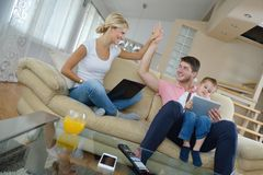 Family at home using tablet computer. Happy young family using tablet computer at modern  home for playing games and education Royalty Free Stock Photo