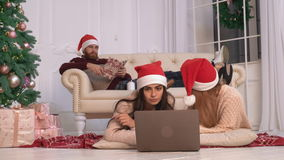 Family at home winter holiday. Friends spend time at home new year eve. Two caucasian women lying on floor using computer. Attractive woman looking on screen stock video footage