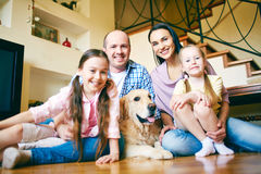 Family at home. A young friendly family of four and their pet looking at camera at home Stock Photo