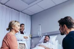 Family visiting hospitalised man. Family in hospital ward with men lying in bed and doctor standing by. Family visiting hospitalised men in ward stock photography