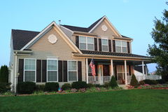 Family House. At suburban residential community with porch and side-loaded garage, and US flag stock photos