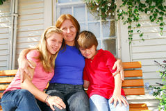 Family at a house. Portrait of a smiling family - mother and children in front of the house Royalty Free Stock Photography