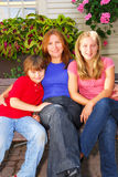 Family at a house. Portrait of a smiling family - mother and children in front of the house Royalty Free Stock Photos