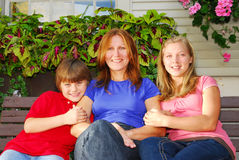Family at a house. Portrait of a smiling family - mother and children in front of the house Royalty Free Stock Image