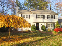 Family house with beautiful front lawn. Upscale family house in Philadelphia suburbs. Front yard with trees and bushes in fall colors Stock Photos