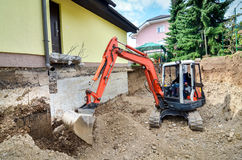 A family house is being rebuilt with the help of an excavator. A big family house is being rebuilt with the help of an excavator. Digging the brick and concrete Royalty Free Stock Photos