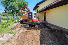 A family house is being rebuilt with the help of an excavator. A big family house is being rebuilt with the help of an excavator. Digging the brick and concrete Stock Photos