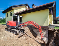 A family house is being rebuilt with the help of an excavator. A family house is being rebuilt and renovated with the help of an excavator. Digger is digging Stock Images