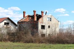 Family house bombarded during war with completely destroyed roof and only chimneys left untouched surrounded with overgrown. Underbrush royalty free stock images