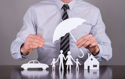 Family, house and car insurance concept. Man holding an umbrella protecting a family, a house and a car stock photo
