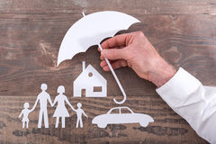Family, house and car insurance concept. House, car and family protected with an umbrella - insurance concept royalty free stock image