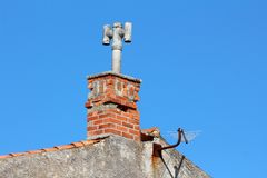 Family house chimney with concrete top in form of closed concrete pipe with two additional pipes on sides and TV antenna mounted. Family house chimney with royalty free stock photos