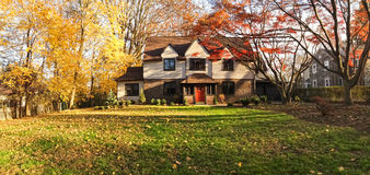Family house with front lawn - panorama. Upscale family house in Philadelphia suburbs. Front yard with trees and bushes in fall colors Stock Photo