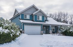 Family house in snow on winter cloudy day. Family house with front yard in snow. Residential house on winter cloudy day royalty free stock images