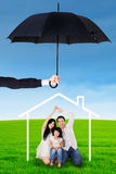 Family with house symbol and umbrella Stock Image