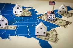 Family houses with dollar bills and central goverment tax over a US map. USA finance and economy concept related to the Tax Cuts and Jobs Act. approved by the stock photos