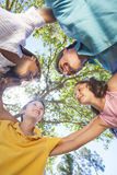 Family Huddle Together Outside In Sunshine. An attractive happy, smiling family of mother, father, son and daughter hugging in a huddle together outside in a Stock Photo