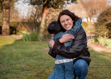 Family Hug. Mother hugging her son.  Big bear hug and mom has a huge smile.  Beautiful moment between mother parent and child.  Outdoors with grass and trees in Stock Photo