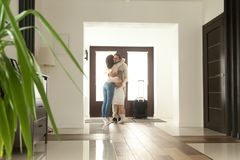 Family hugging father arrived came home returning after business. Woman and little girl embracing men standing in hall, wife meeting husband just arrived came royalty free stock photography