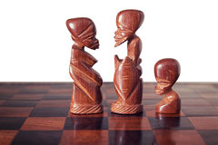 Family with husband , wife and a son, represented by three pieces of wooden chess, king, queen and pawn , facing each other. Stock Photography